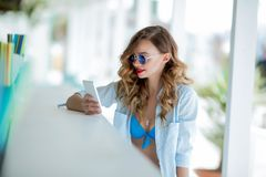Beautiful brunette on a summer terrace by the sea, in a summer cafe. Talking on a cell phone. With makeup and hairdo, a royalty free stock images