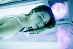 Beautiful brunette sunbathing in solarium Stock Photos