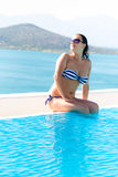 Beautiful brunette at sunny swimming pool Stock Photo