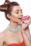 Beautiful brunette sweet woman with colorful make up and nail po. Lish, and cute bun hairstyle. Eating donut. white background Stock Images