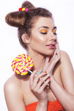 Beautiful brunette sweet woman with colorful make up and nail po. Lish, and cute bun hairstyle. Eating lollipop. white background Royalty Free Stock Images