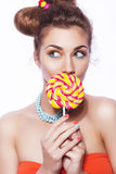 Beautiful brunette sweet woman with colorful make up and nail po. Lish, and cute bun hairstyle. Eating lollipop. white background Stock Photo