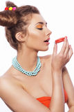 Beautiful brunette sweet woman with colorful make up and nail po. Lish, and cute bun hairstyle. Eating macaroon. white background Royalty Free Stock Image
