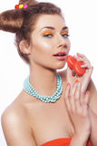 Beautiful brunette sweet woman with colorful make up and nail po. Lish, and cute bun hairstyle. Eating macaroon. white background Royalty Free Stock Images