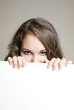 Beautiful brunette teen hiding behind sign. Closeup portrait of a beautiful brunette teen hiding behind empty white sign Stock Photos