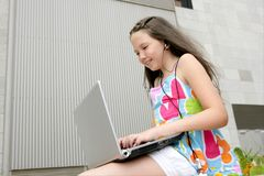 Beautiful brunette teen little girl laptop city Stock Photo