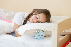 Beautiful brunette teenage girl sleeping on alarm clock the pill. Portrait of beautiful brunette teenage girl sleeping on alarm clock the pillow Stock Image