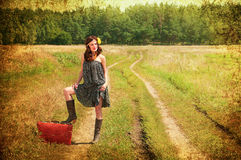 Beautiful brunette. Travel. Beautiful brunette with a suitcase in the countryside. Photos in the old style Stock Images