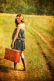 Beautiful brunette. Travel. Beautiful brunette with a suitcase in the countryside. Photos in the old style Stock Image