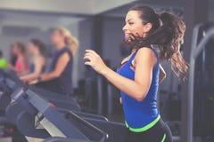 Beautiful brunette on a treadmill Stock Photos