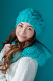 Beautiful brunette in a turquoise knitted hat and scarf smiling Stock Photo