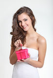 Beautiful brunette unwrapping a gift Royalty Free Stock Images