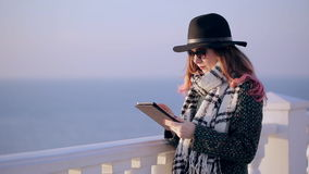 Beautiful brunette using digital tablet touch screen. Hipster girl with tablet computer on the beach stock video footage