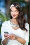 Beautiful brunette using her smartphone Stock Photos