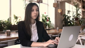 Beautiful brunette using laptop in cafe. Business woman conducts business correspondence on the Internet. Long black hair. Startup, work in a cafe concept stock video footage
