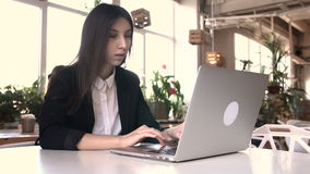Beautiful brunette using laptop in cafe. Business woman smiling, straightening hair. Long black hair. Startup, work in a cafe concept stock video footage