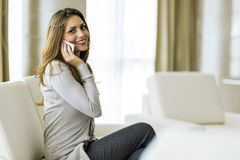 Beautiful brunette using a phone in a stylish house Stock Image