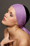 Beautiful brunette in a violet scarf Stock Images