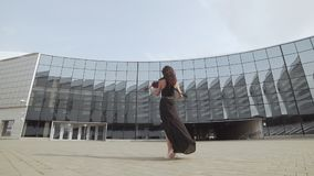 Beautiful violinist in black dress near glass building. Urban art concept. Beautiful brunette violinist in black dress near glass building in slowmotion. Urban stock video footage
