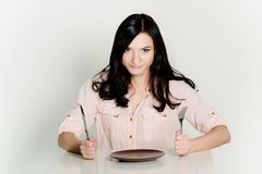 Beautiful brunette waiting for food at a restaurant. Royalty Free Stock Photo