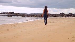 Beautiful brunette walking along the water by the beach
