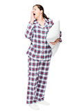Beautiful brunette wants to sleep, yawns, dressed in pajamas Royalty Free Stock Photo