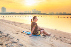 Beautiful brunette watching sunrise on the beach Royalty Free Stock Photography