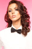 Beautiful brunette wearing a black tie bow and white shirt Stock Photo