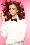 Beautiful brunette wearing a black tie bow and white shirt Stock Photos