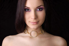 Beautiful brunette wearing golden necklace Stock Image