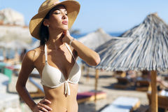 Beautiful brunette wearing hat on beach Stock Photography