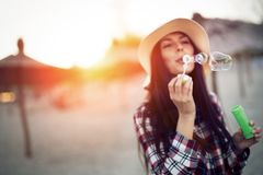 Beautiful brunette wearing hat blowing dreamy bubbles Royalty Free Stock Photography