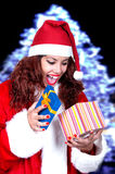 Beautiful brunette wearing santa claus with gift Stock Photography