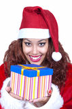Beautiful brunette wearing santa claus with gift Royalty Free Stock Photography