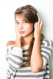 Beautiful brunette wearing silver headphones. Royalty Free Stock Image