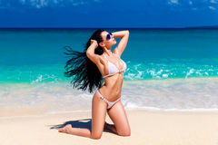 Beautiful  brunette in white bikini on a tropical beach Royalty Free Stock Photos