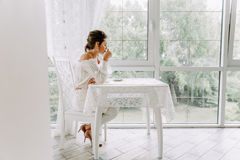 Beautiful brunette in a white blouse, drinking coffee on the bright terrace royalty free stock image