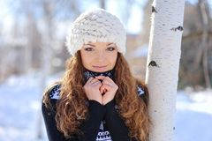 Beautiful brunette in a white hat standing in a park near a tree in winter.  Royalty Free Stock Photos
