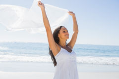 Beautiful brunette in white sun dress holding sarong Stock Image
