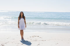 Beautiful brunette in white sun dress walking from the ocean Royalty Free Stock Photography