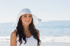 Beautiful brunette in white sunhat looking away. At the beach Stock Photography