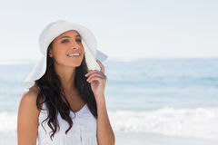 Beautiful brunette in white sunhat looking away and touching hat Royalty Free Stock Images