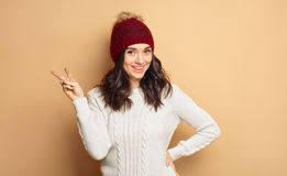 Beautiful brunette in winter outfit isolated over beige background Royalty Free Stock Photography