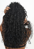 Beautiful brunette woman. Showing off her long curly hair on grey background. Not isolated Royalty Free Stock Photography