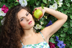 Beautiful brunette woman with apple next to green hedge Stock Photos