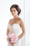 Beautiful brunette woman as bride with pink wedding bouquet on white royalty free stock photos