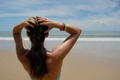 Beautiful brunette woman on the beach. Back of a beautiful brunette woman on the beach looking out to sea stock image