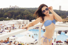 Beautiful brunette woman on the beach in pool alone relaxing in Royalty Free Stock Photos