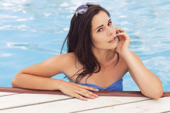 Beautiful brunette woman on the beach in pool alone relaxing in Royalty Free Stock Images