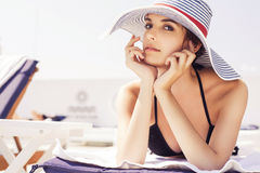 Beautiful brunette woman on the beach in pool alone relaxing in Stock Photography